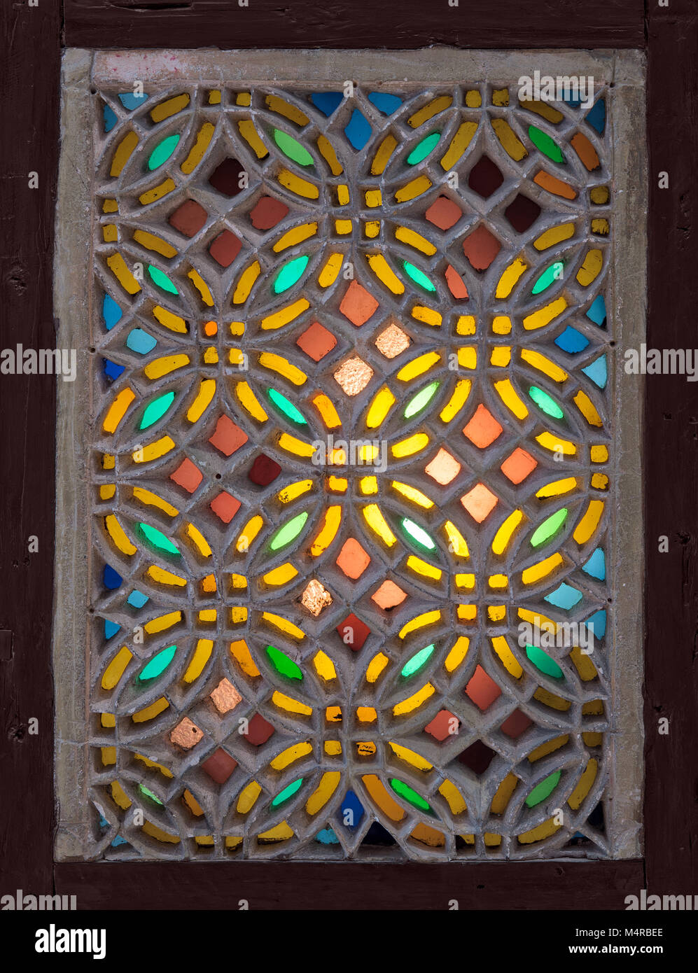 Perforated stucco window decorated with colorful stain glass with geometrical circular patterns, one of the traditions - Stock Image