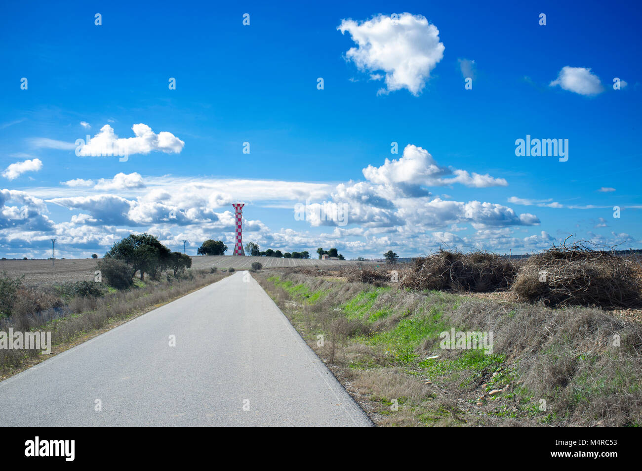 Road to Irrigation water tank. Concrete tower made for store irrigation water, Vegas Bajas del Guadiana, Extremadura, - Stock Image