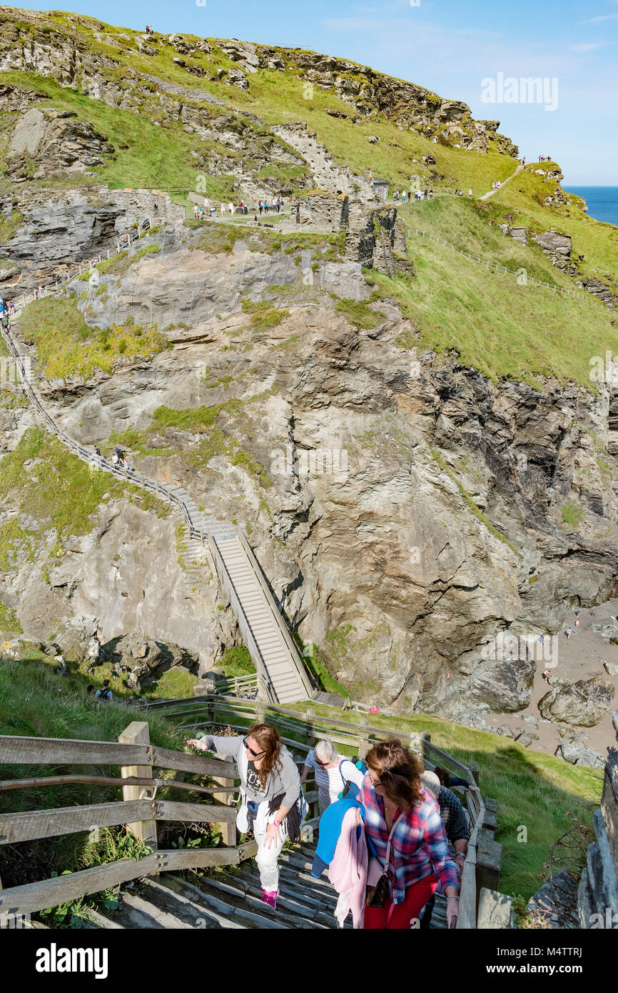 visitors navigating the steep steps at tintagel castle on the north coast of cornwall, england, britain, uk. - Stock Image