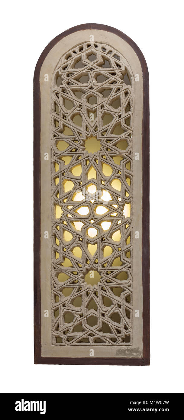 Perforated arched stucco window decorated with stain glass with geometrical patterns, one of the traditions of the - Stock Image