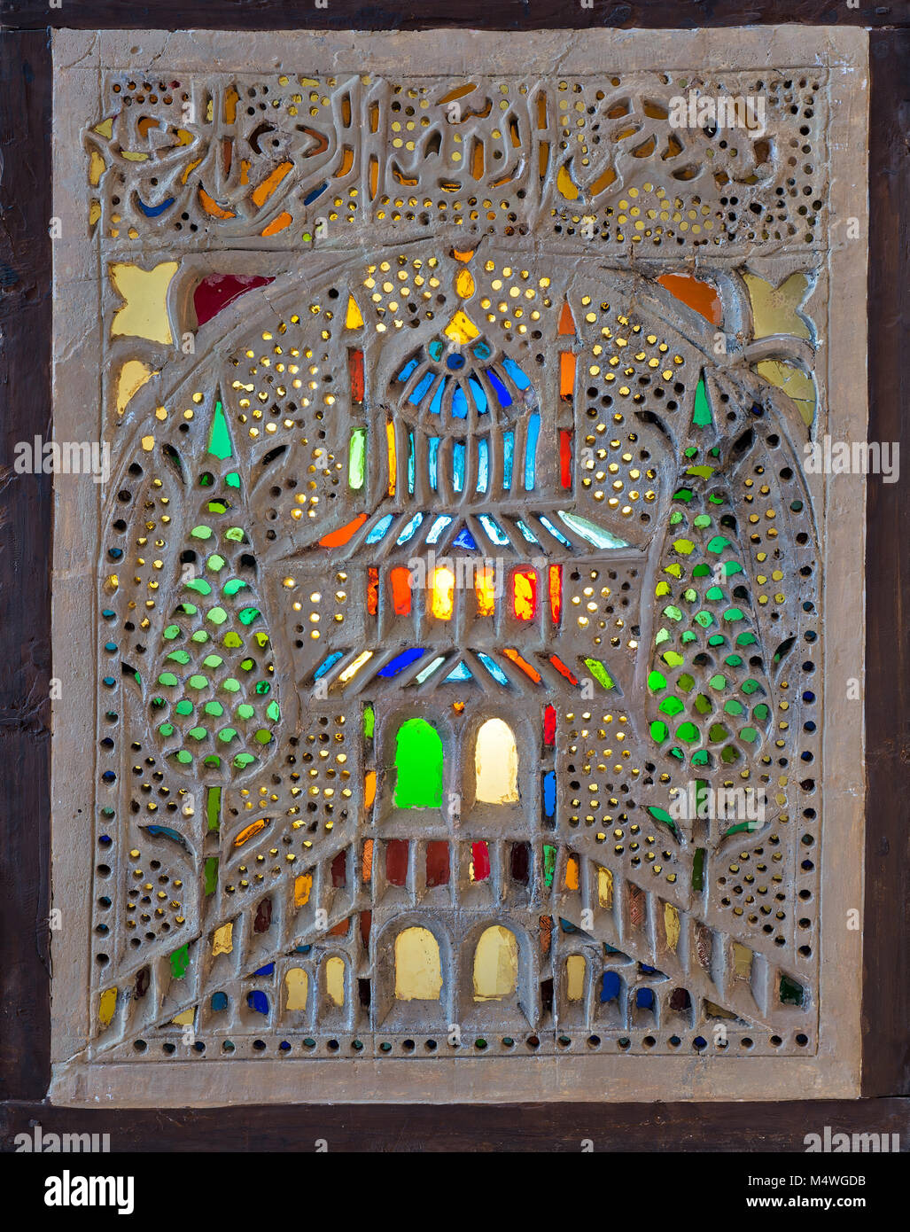 Perforated stucco window decorated with colorful stain glass with floral patterns, one of the traditions of the - Stock Image