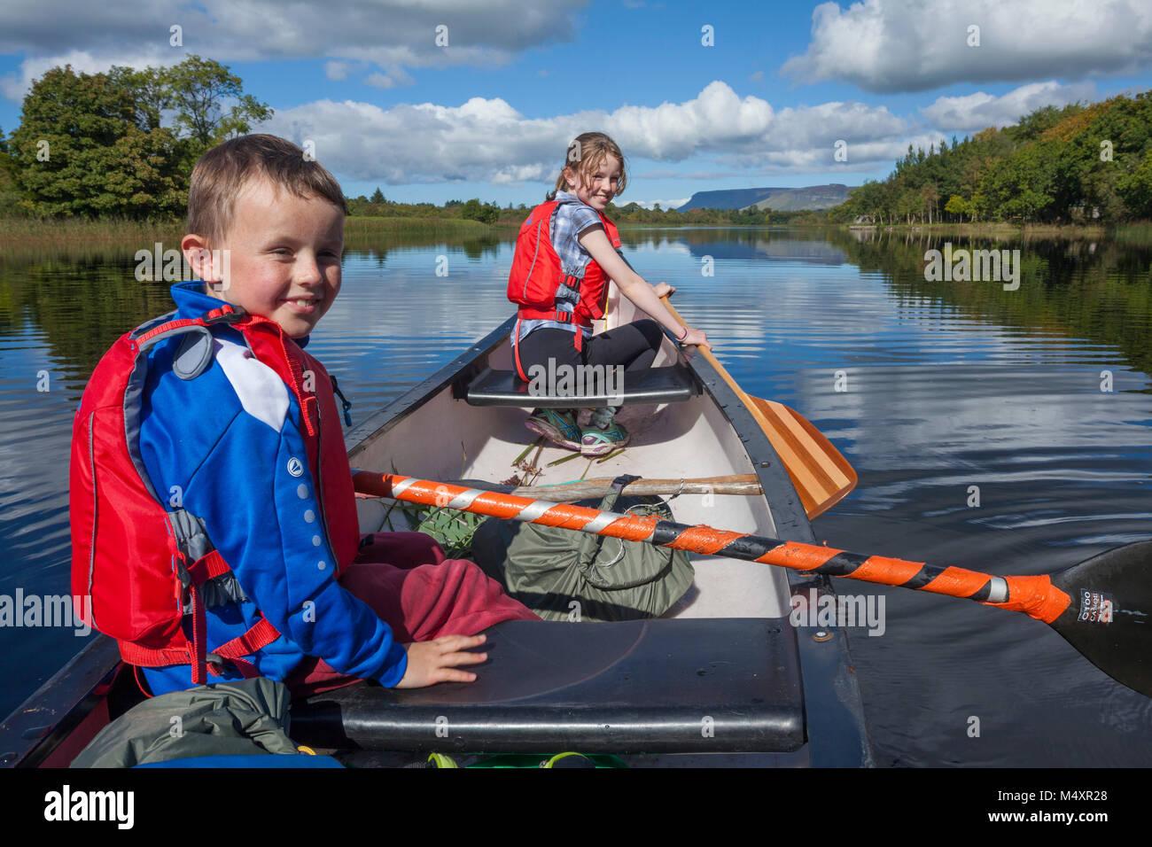 Family canoeing the Garavogue River to Lough Gill, Sligo town, County Sligo, Ireland. - Stock Image