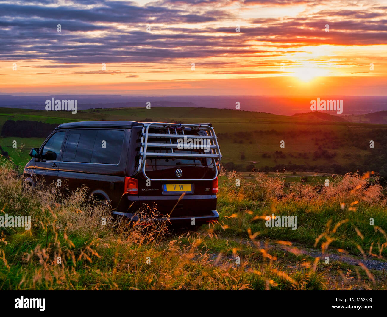 VW California camper van parked up for the night at a free glamping location the occupants enjoying the lovely sunset - Stock Image