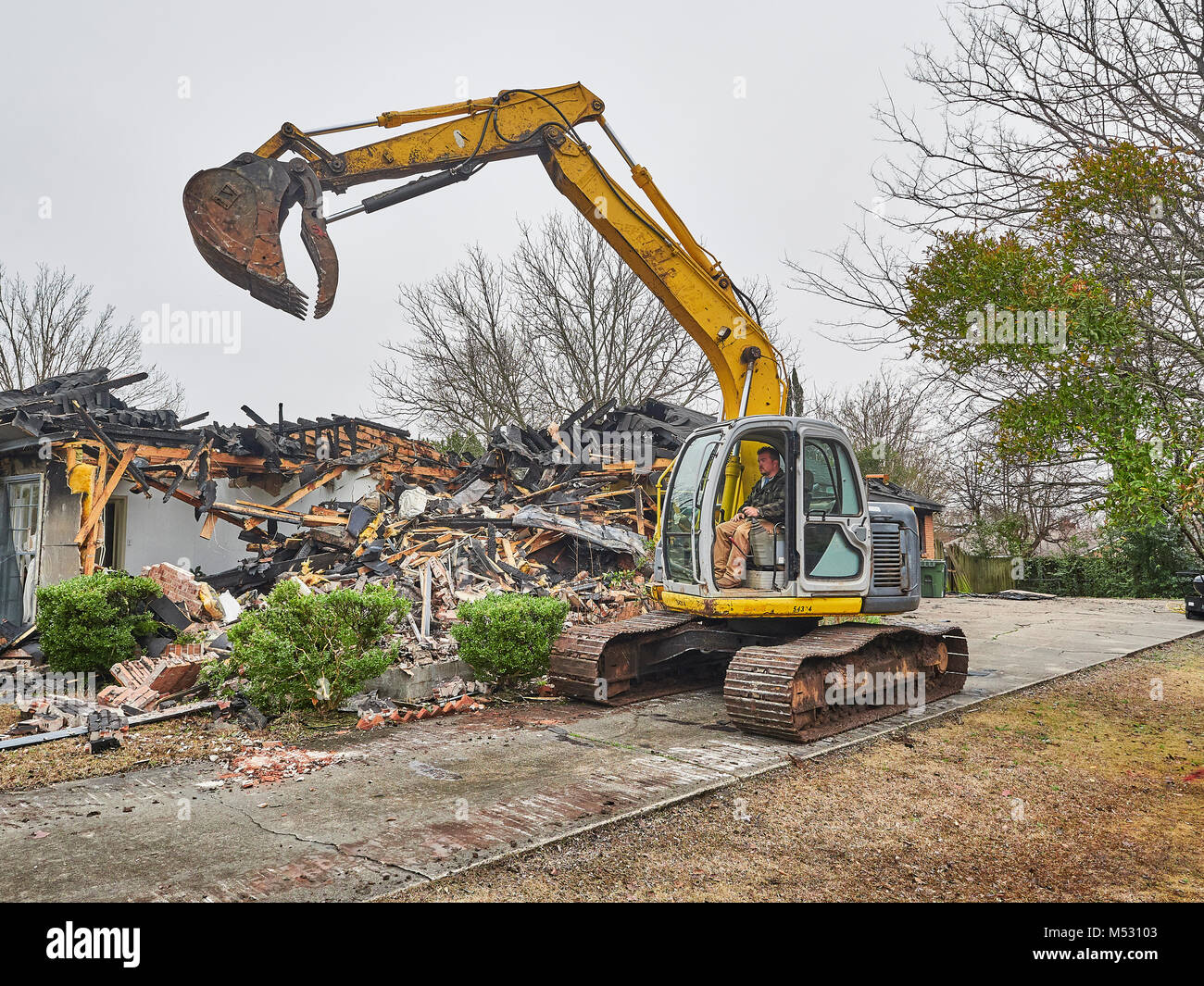 Workers using heavy duty excavator to help demolish a house that caught fire and burned in Montgomery Alabama, USA. - Stock Image
