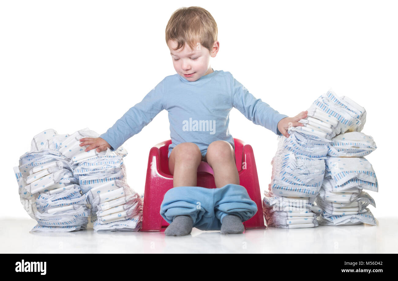 Happy baby boy sitting on chamber pot tearing down diaper piles. Potty training concept - Stock Image