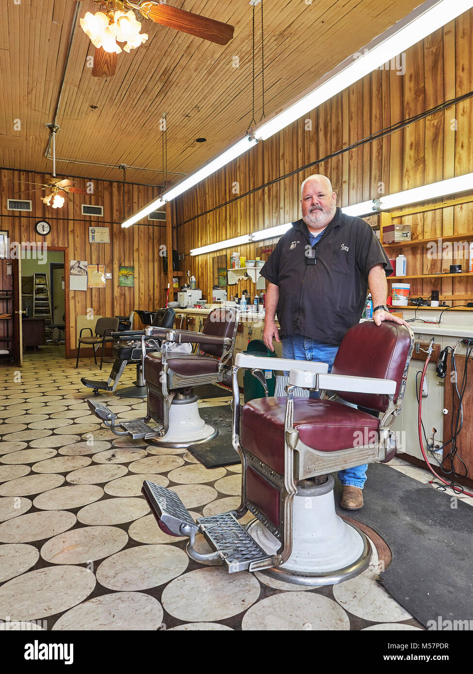 Small town male barber standing next to an old antique barber chair in a vintage barber shop, in Prattville Alabama, - Stock Image