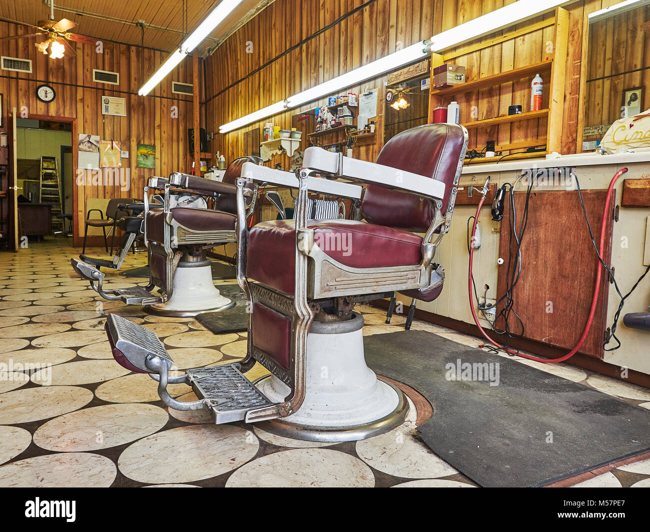 Old vintage, barber chairs in an empty small town barber shop interior in Prattville Alabama, USA. - Stock Image