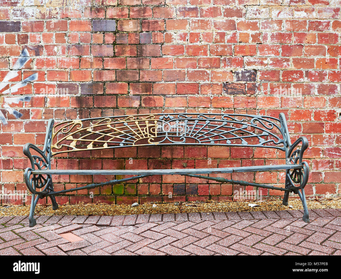 Single iron metal unoccupied park bench against an old brick wall with brick pavers in front. - Stock Image