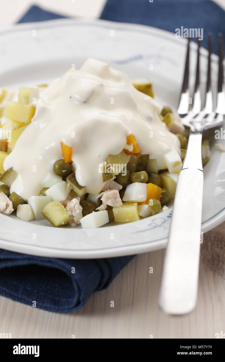 Russian salad in white plate closeup - Stock Image