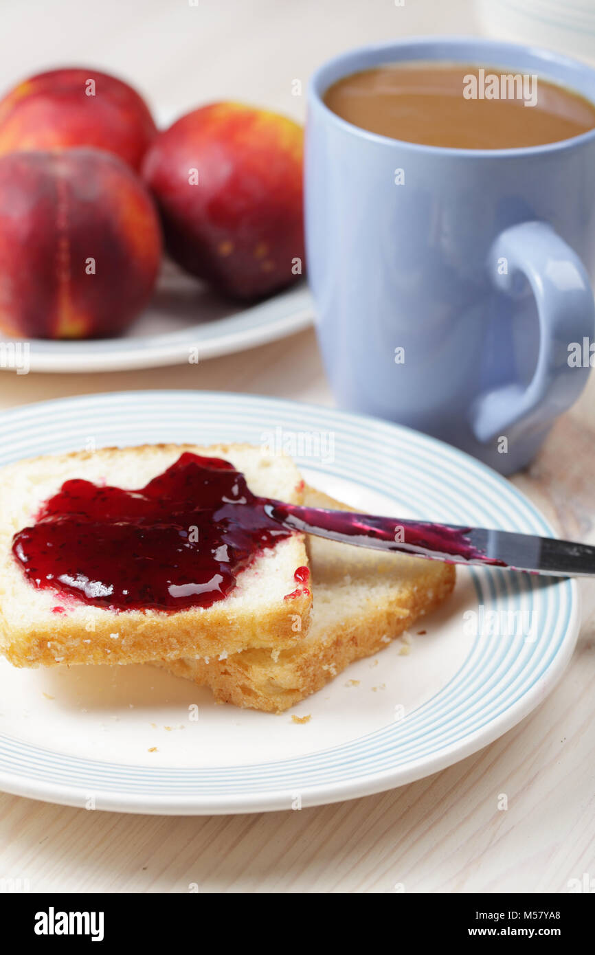 Breakfast with toasts, black currant jelly, peaches and coffee - Stock Image