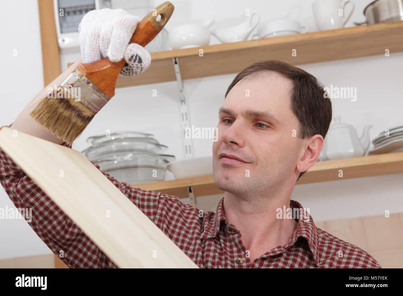 Man varnishing wood shelves for kitchen renovation - Stock Image