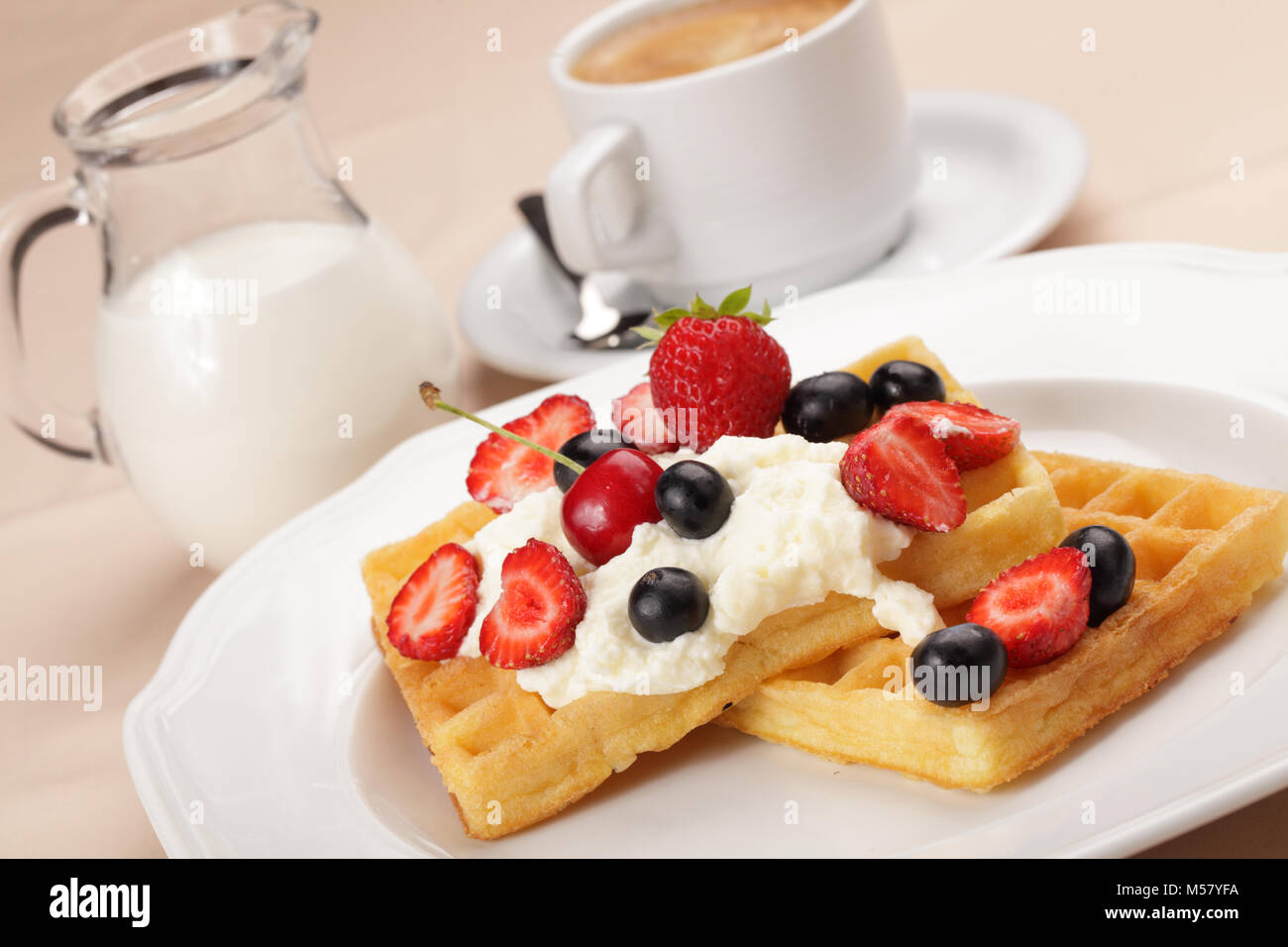 Belgian waffles with whipped cream, strawberry, cherry and blueberry - Stock Image