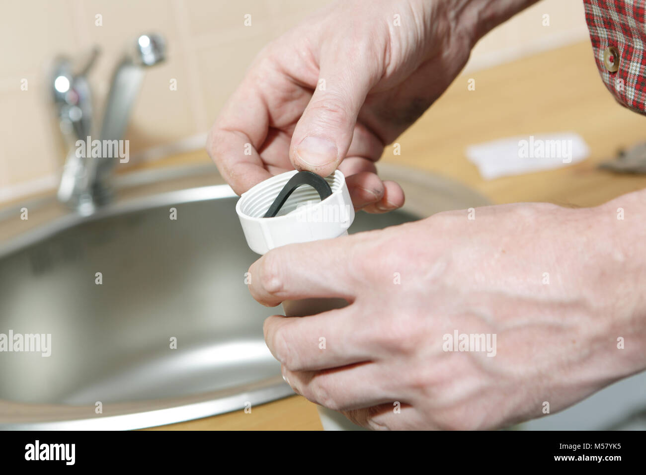 Plumber installing a rubber washer to the sewer pipe of a drain for a kitchen sink - Stock Image