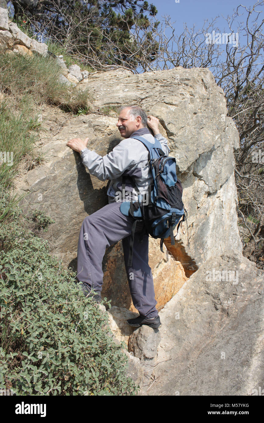Mature man with backpack climbing on rock - Stock Image