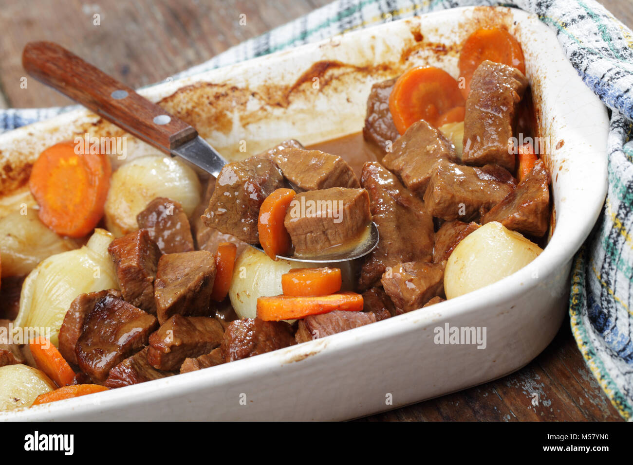 Beef bourguignon in white casserole on a rustic table - Stock Image