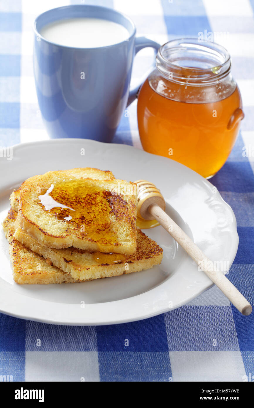 French toasts with honey and a cup of milk - Stock Image