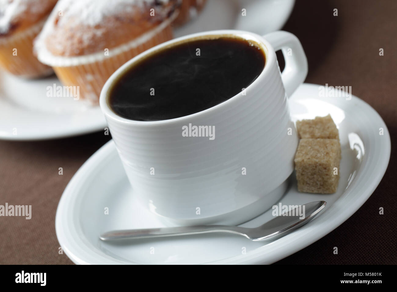 Cup of black coffee against muffins - Stock Image