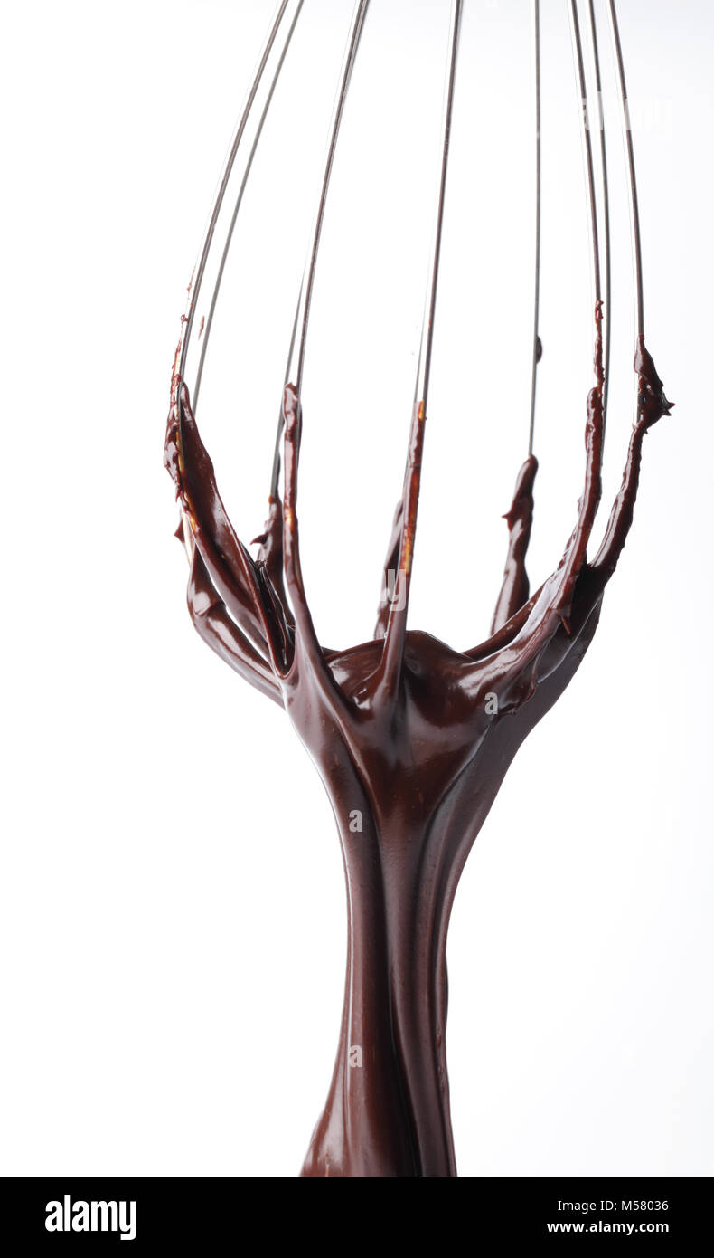Wishk with liquid chocolate isolated on white - Stock Image