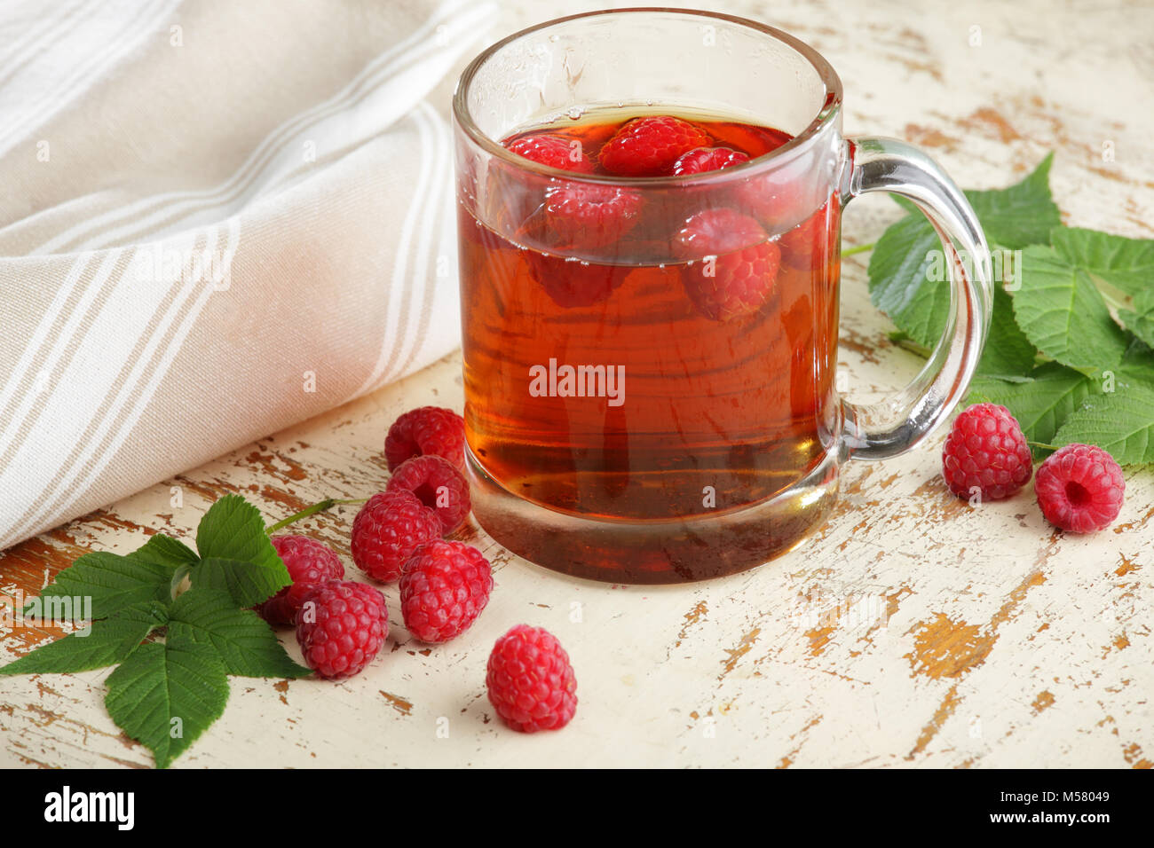 Raspberry tea in a glass cup and scattered berries - Stock Image