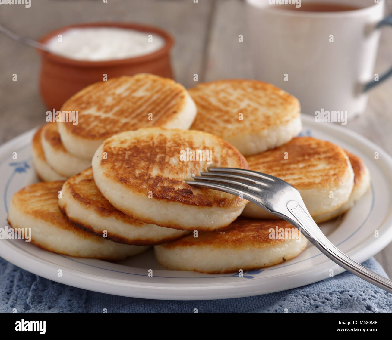 Syrniki, the traditional Russian cheese pancakes on a rustic table - Stock Image