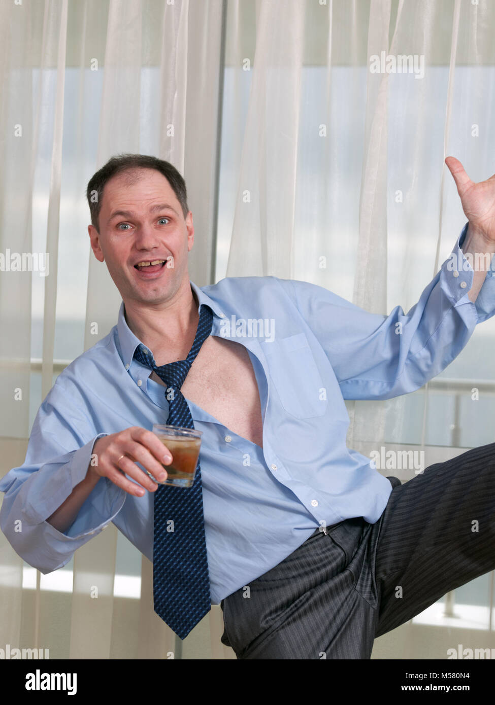 Drunk businessman holding a glass - Stock Image