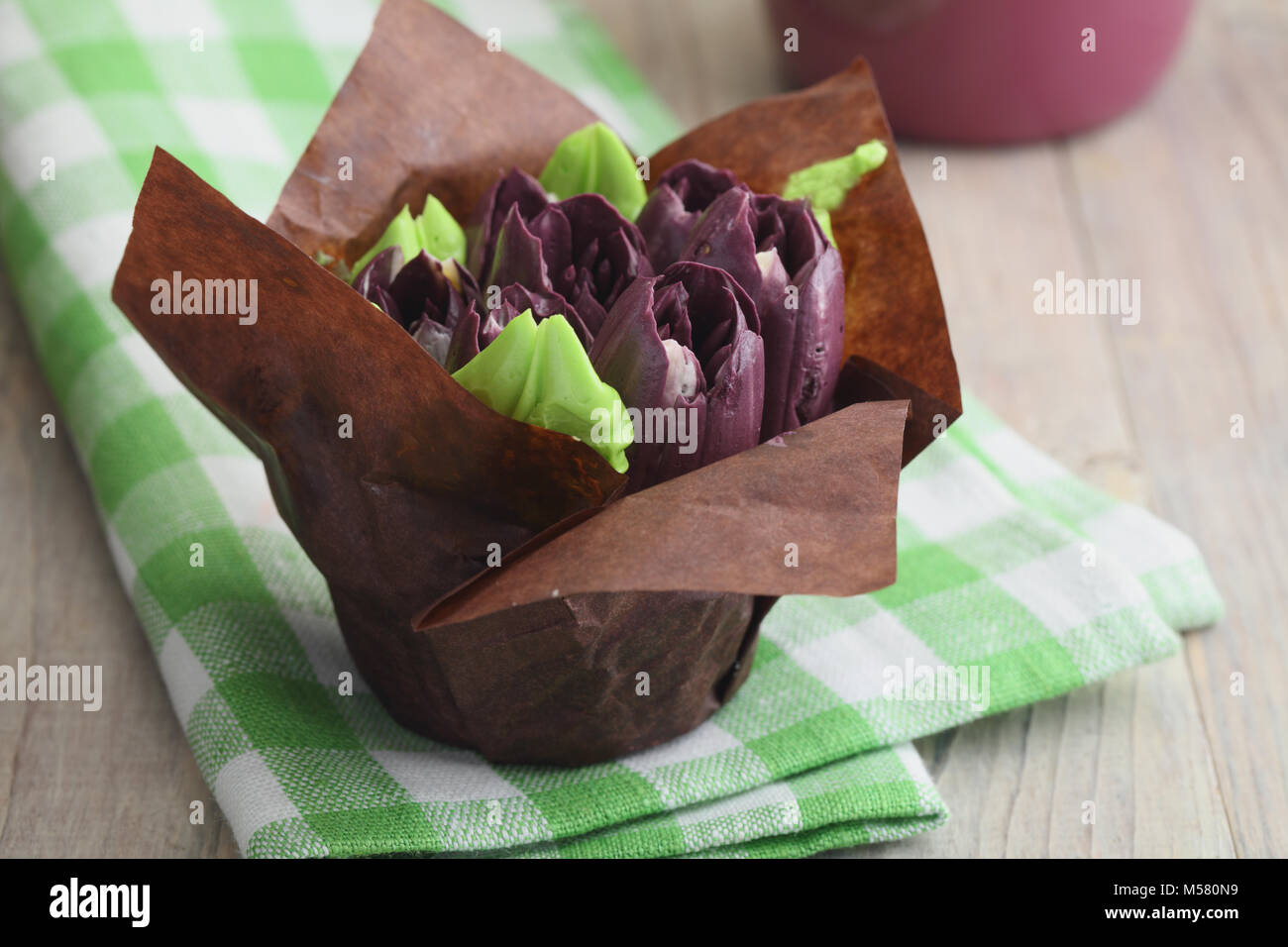 Easter cupcake in a baking paper topped with buttercream tulip flowers - Stock Image