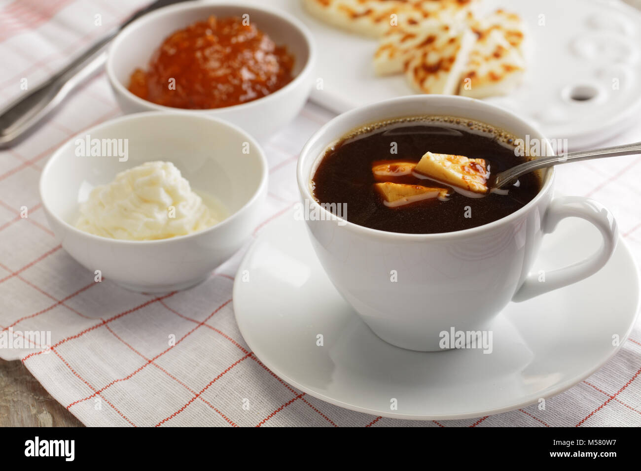 Swedish breakfast with mini farmer cheeses, cloudberry jam, whipped cream, and a cup of coffee - Stock Image