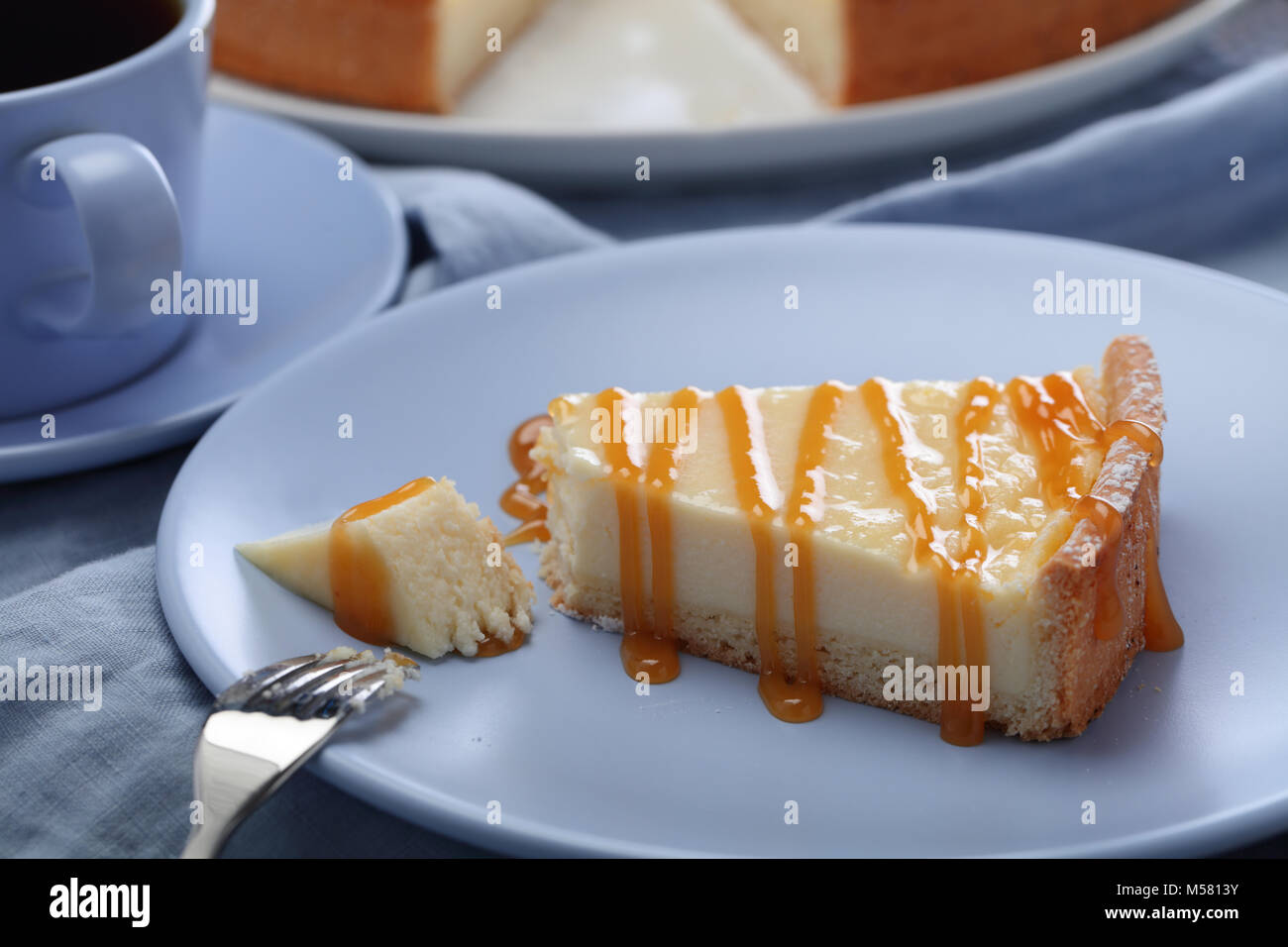 Slice of cheesecake with caramel sauce - Stock Image
