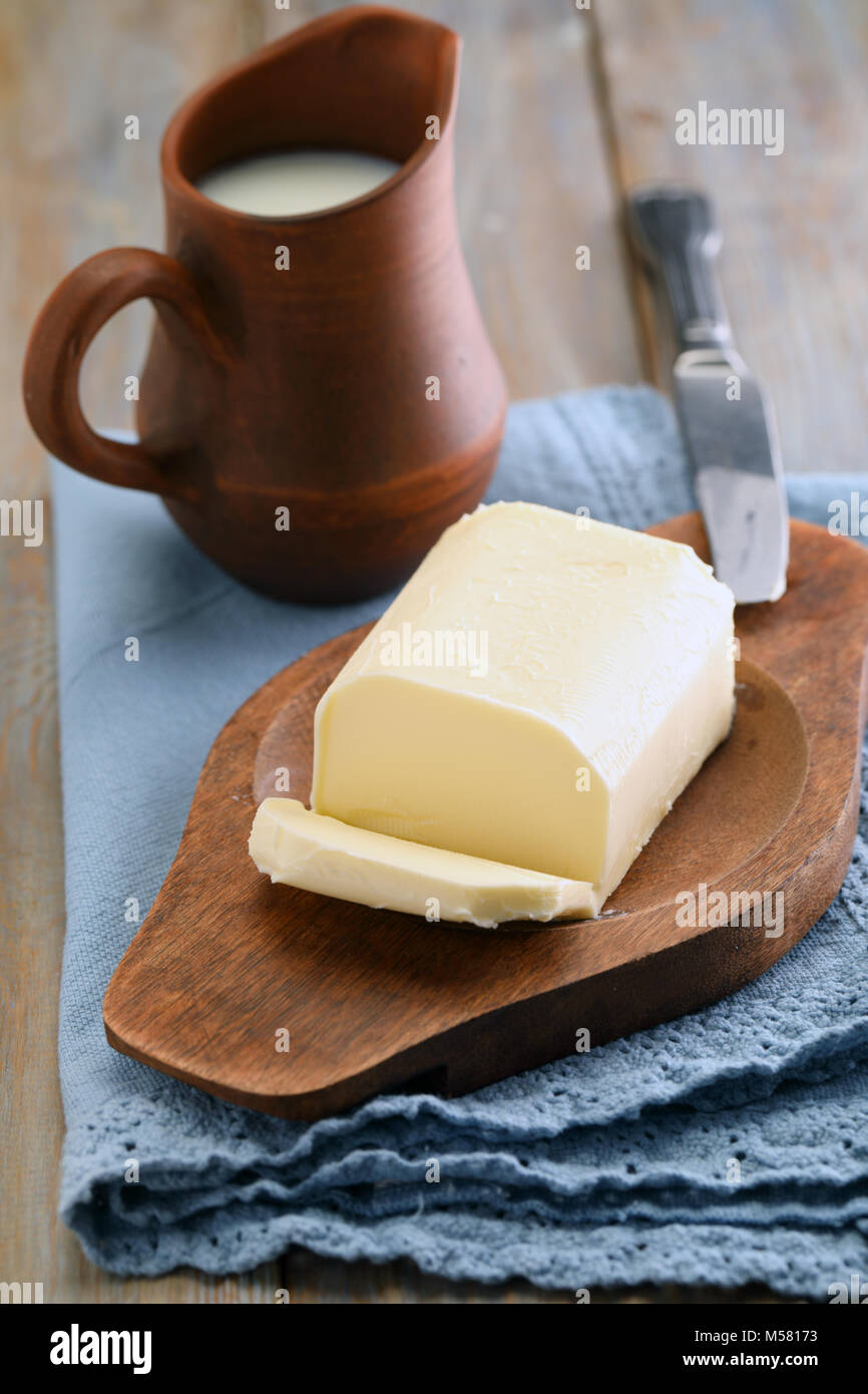 Block of butter and a jug of milk on a rustic table - Stock Image