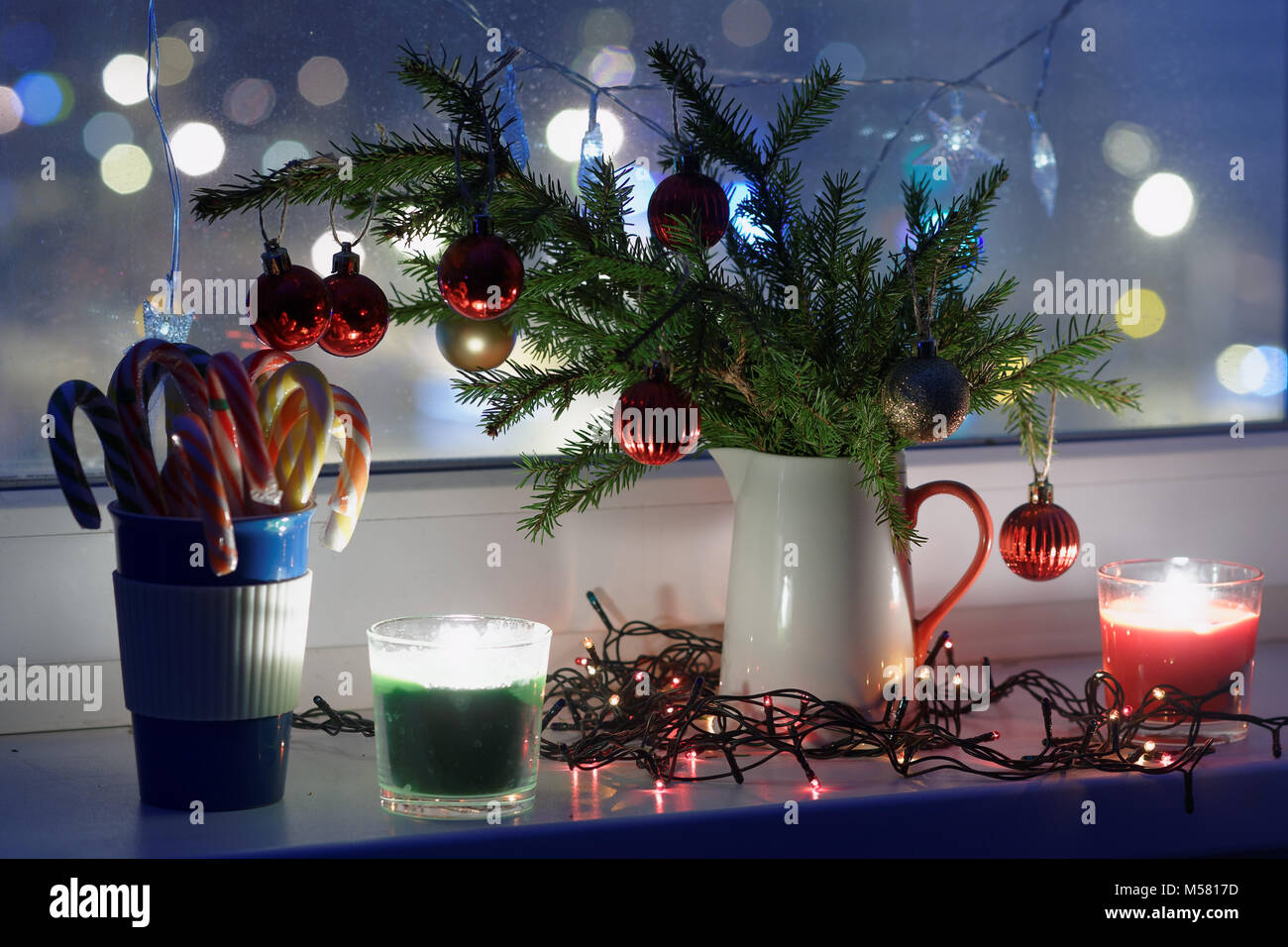 Christmas decorations and candles on a window sill - Stock Image