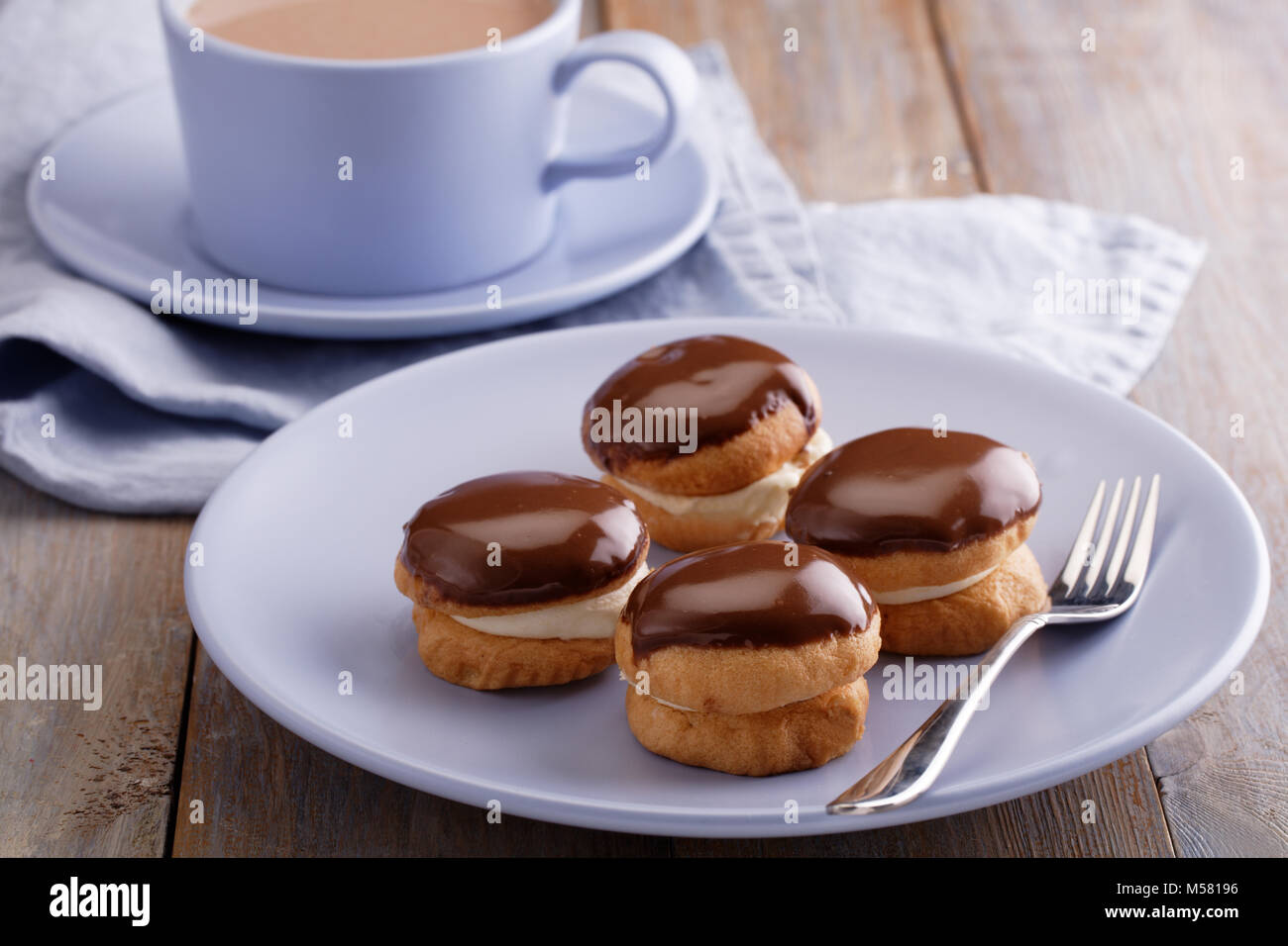 French cakes covered with chocolate on a rustic table - Stock Image