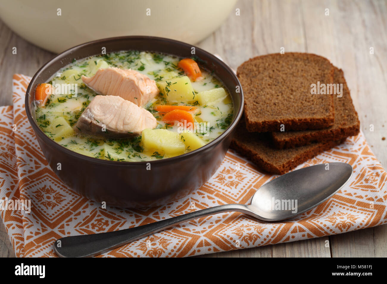 Finnish fish soup kalakeitto with salmon and cream on a rustic table - Stock Image