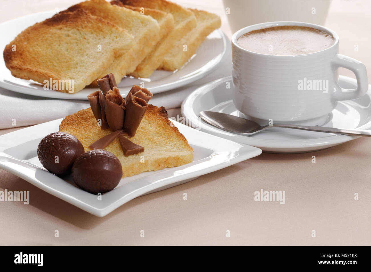 Breakfast with black coffee, toasts, and chocolate - Stock Image