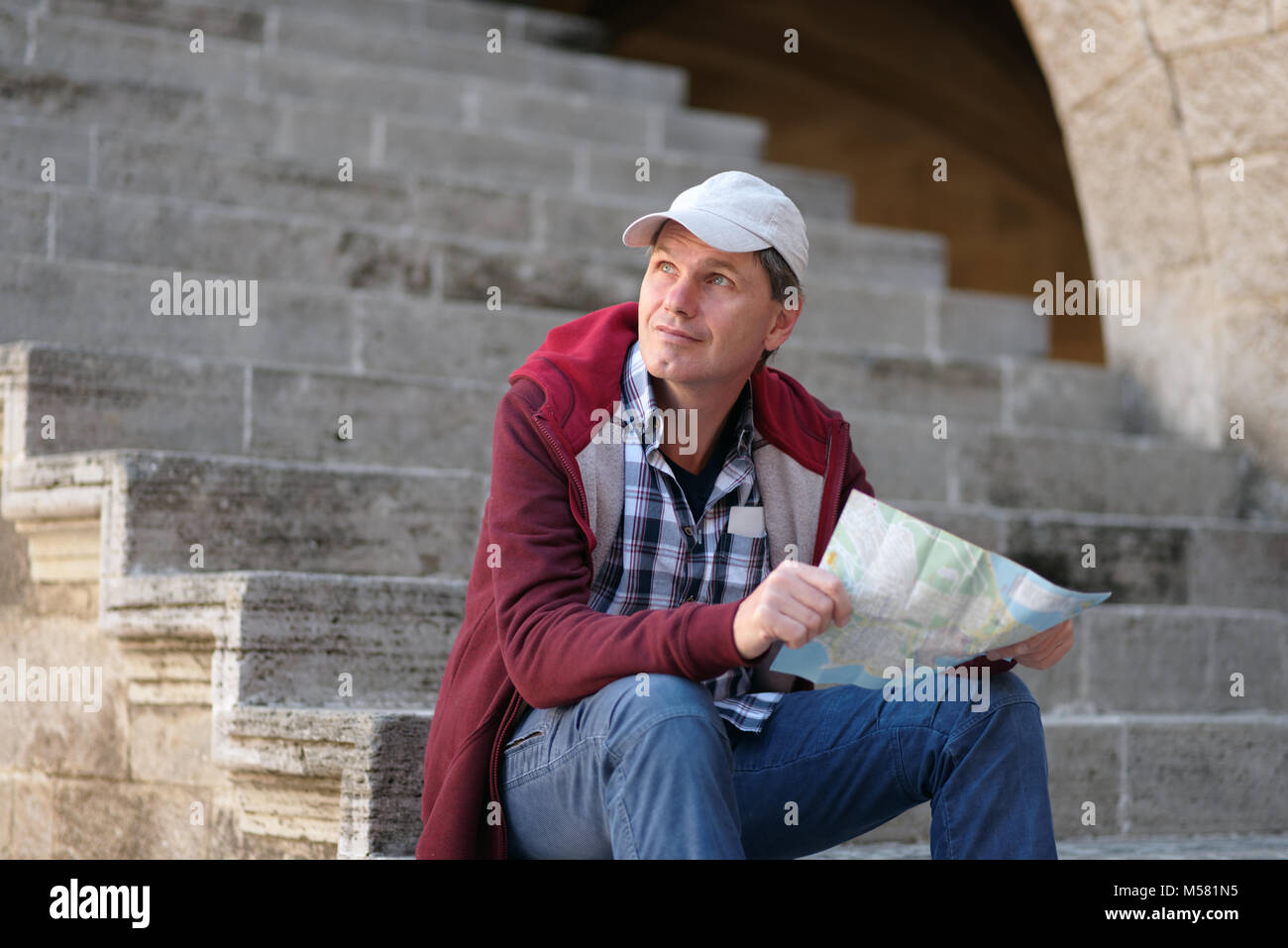 Tourist with city plan sitting on a staircase on Rhodes - Stock Image