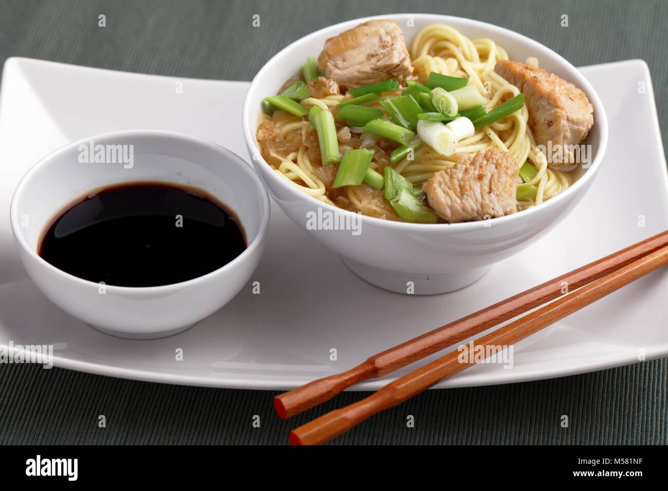 Udon noodle soup with chicken meat, green onion, and soy sauce - Stock Image