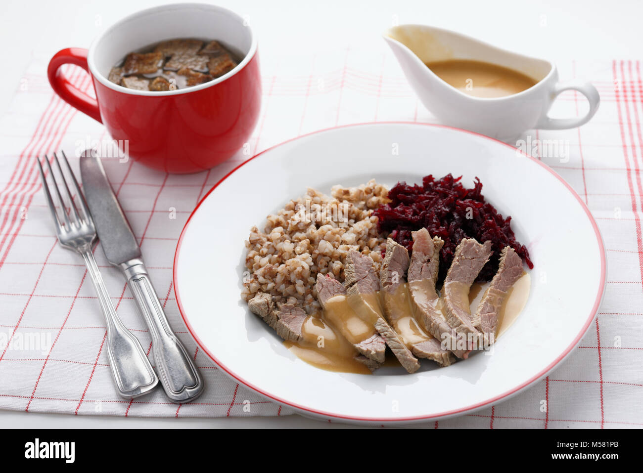 Boiled beef meat with buckwheat porridge, beetroot salad, and beef broth - Stock Image