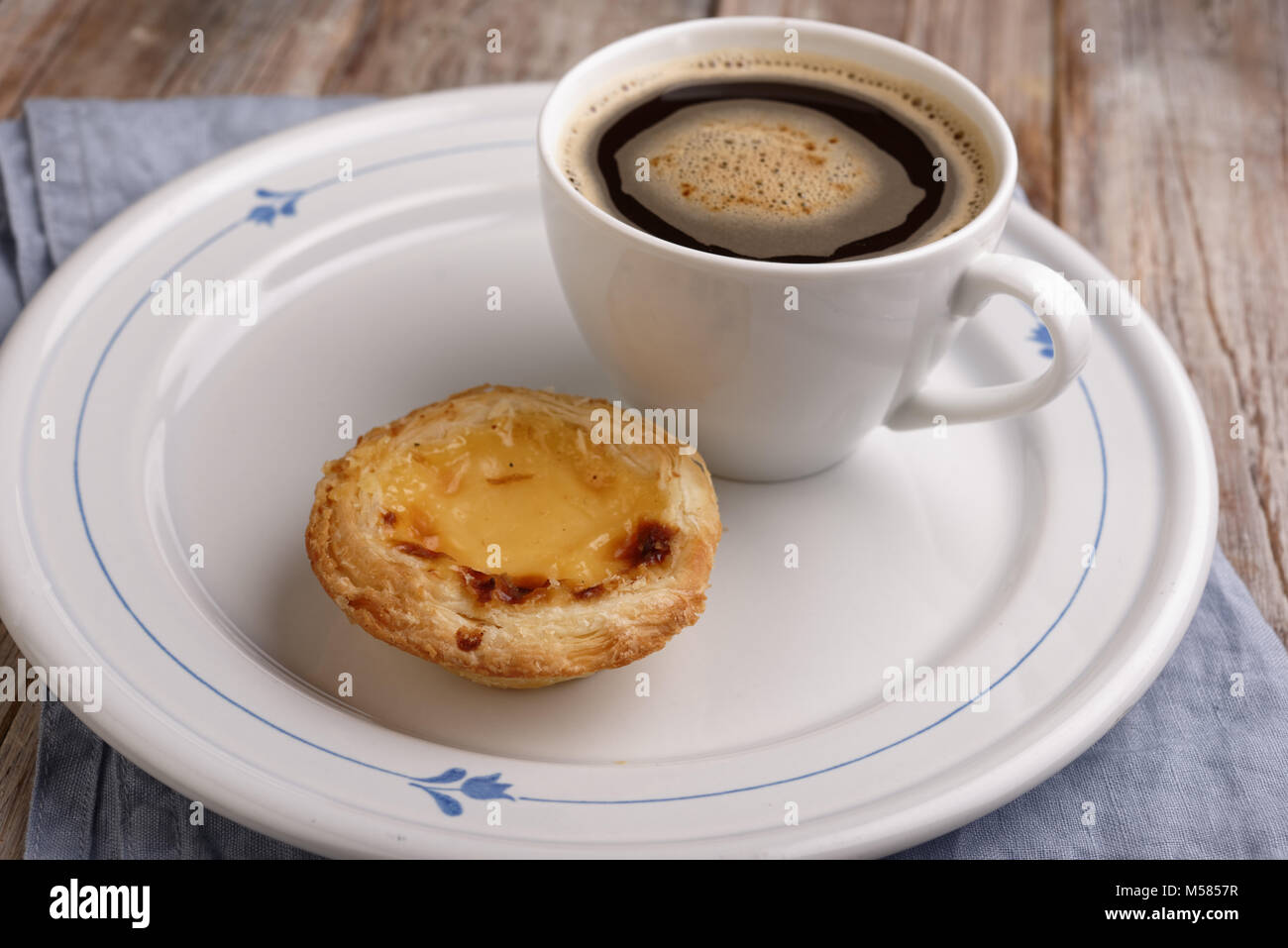 Portuguese egg tart pastry Pastel de nata on a plate with a cup of black coffee - Stock Image