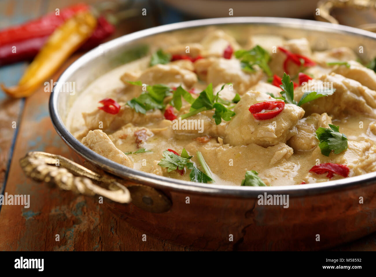 Chicken curry in a rustic cooking pan - Stock Image