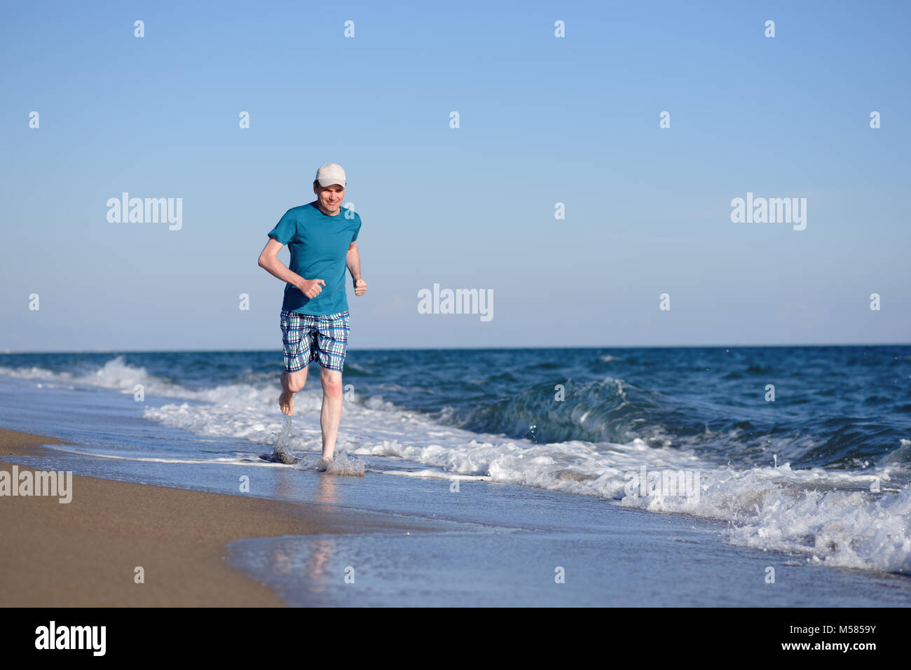 Barefoot mature man during jogging on a beach - Stock Image