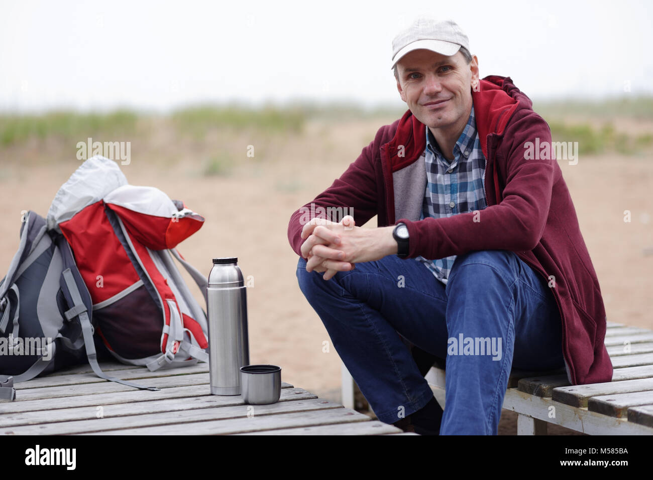 Man with backpack resting on a beach - Stock Image