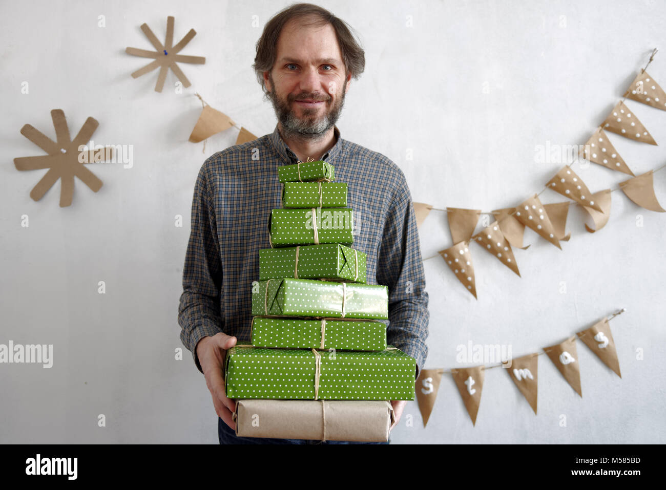 Mature man with stack of gift boxes in a room decorated for Christmas - Stock Image