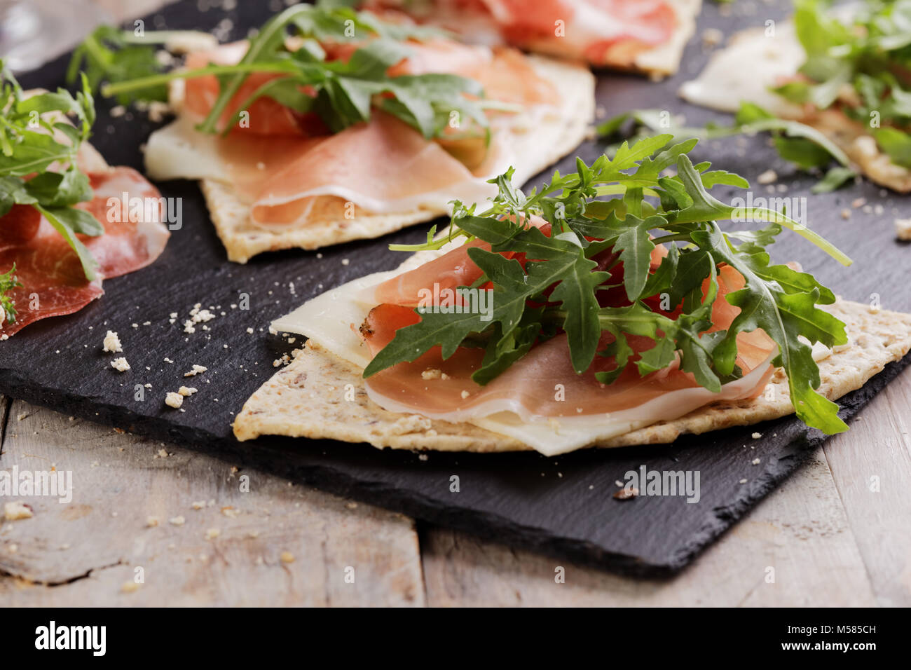 Sandwiches with Prosciutto, sliced cheese, and rocket salad on wedges of piadina - Stock Image