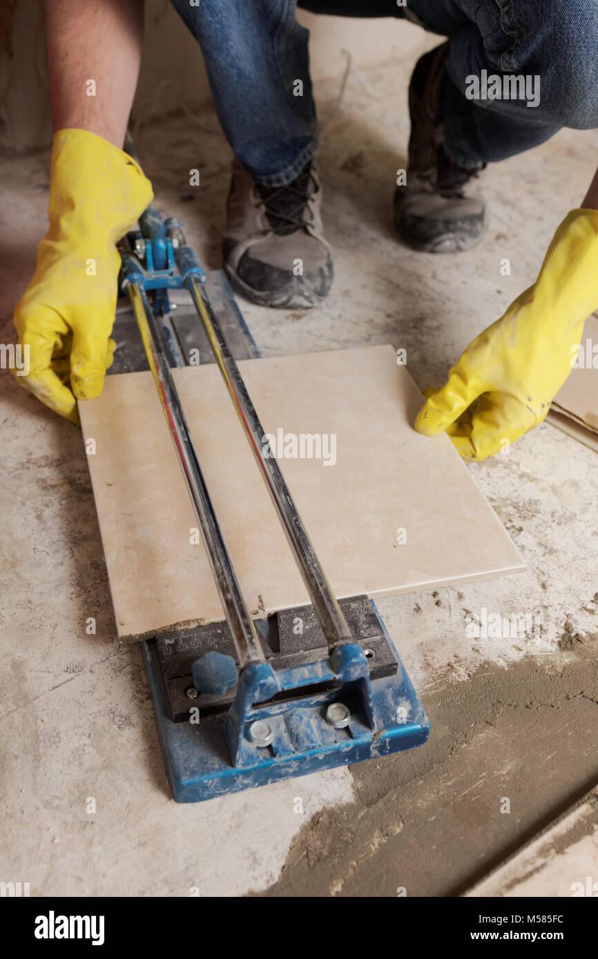 Tiler cutting ceramic tiles during floor installation - Stock Image