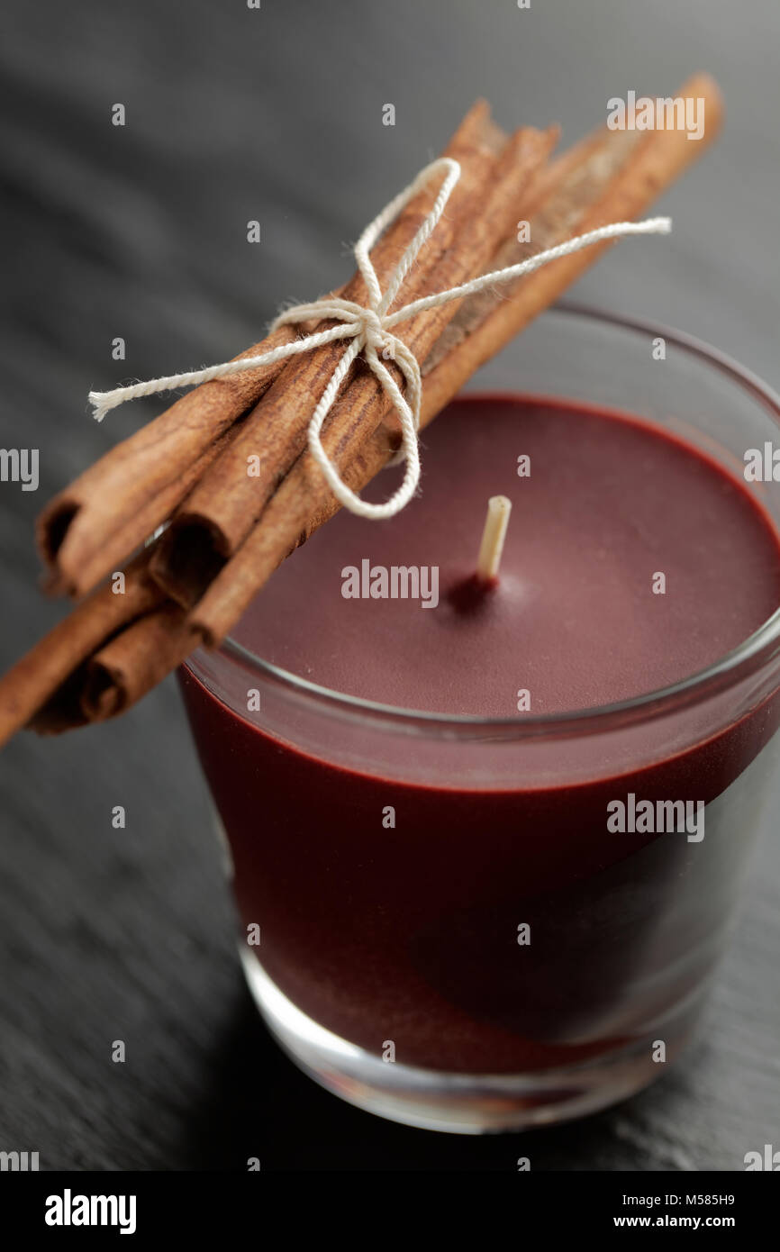 Aromatic candle and cinnamon sticks - Stock Image