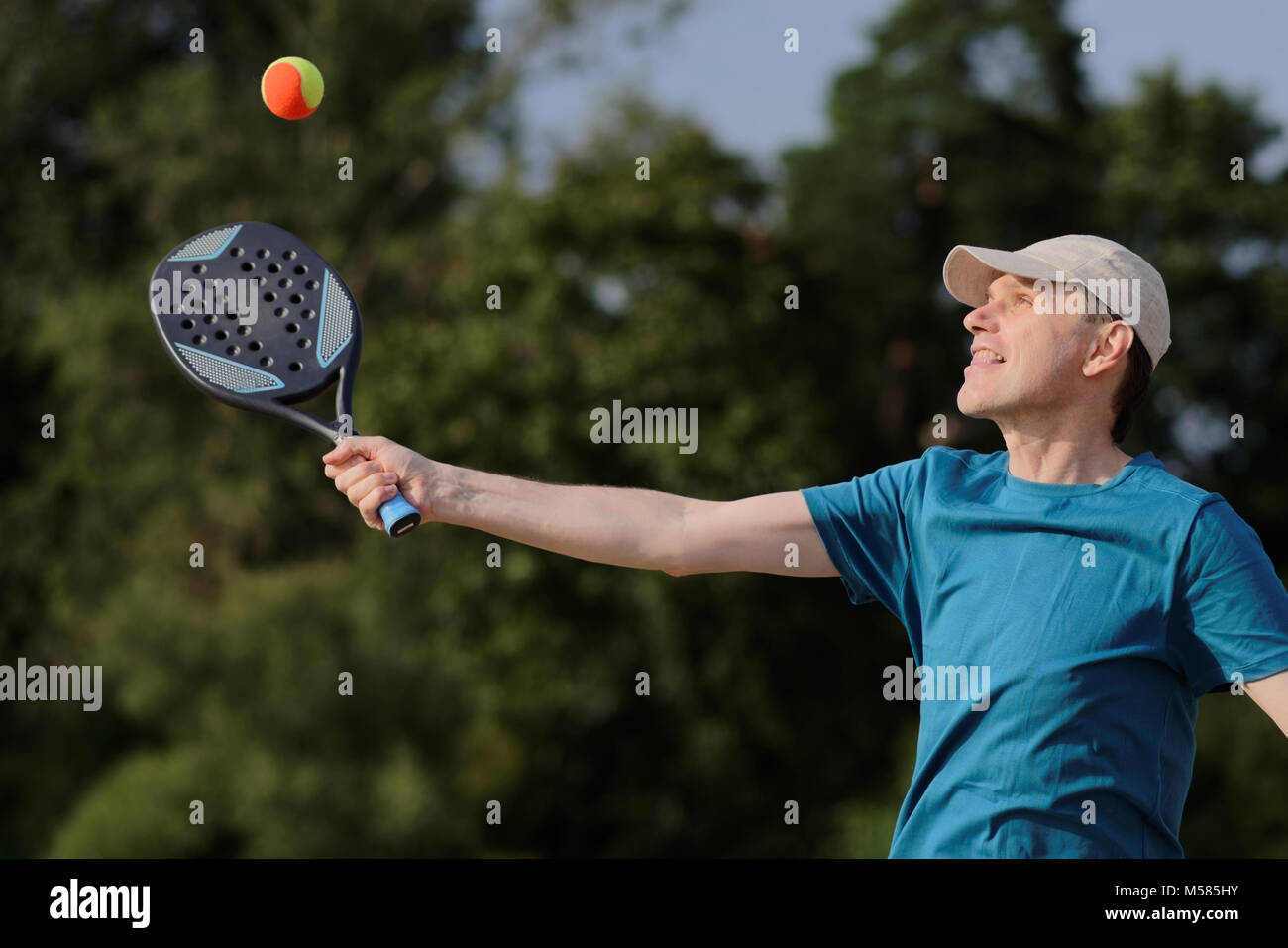 Mature man playing beach tennis on a beach - Stock Image