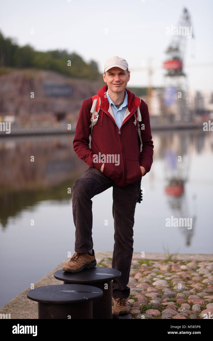 Tourist with backpack standing on waterfront in Turku, Finland - Stock Image
