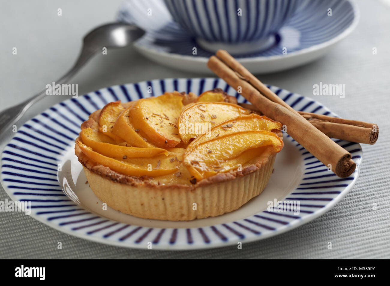 Peach tart and cinnamon sticks on a plate closeup - Stock Image
