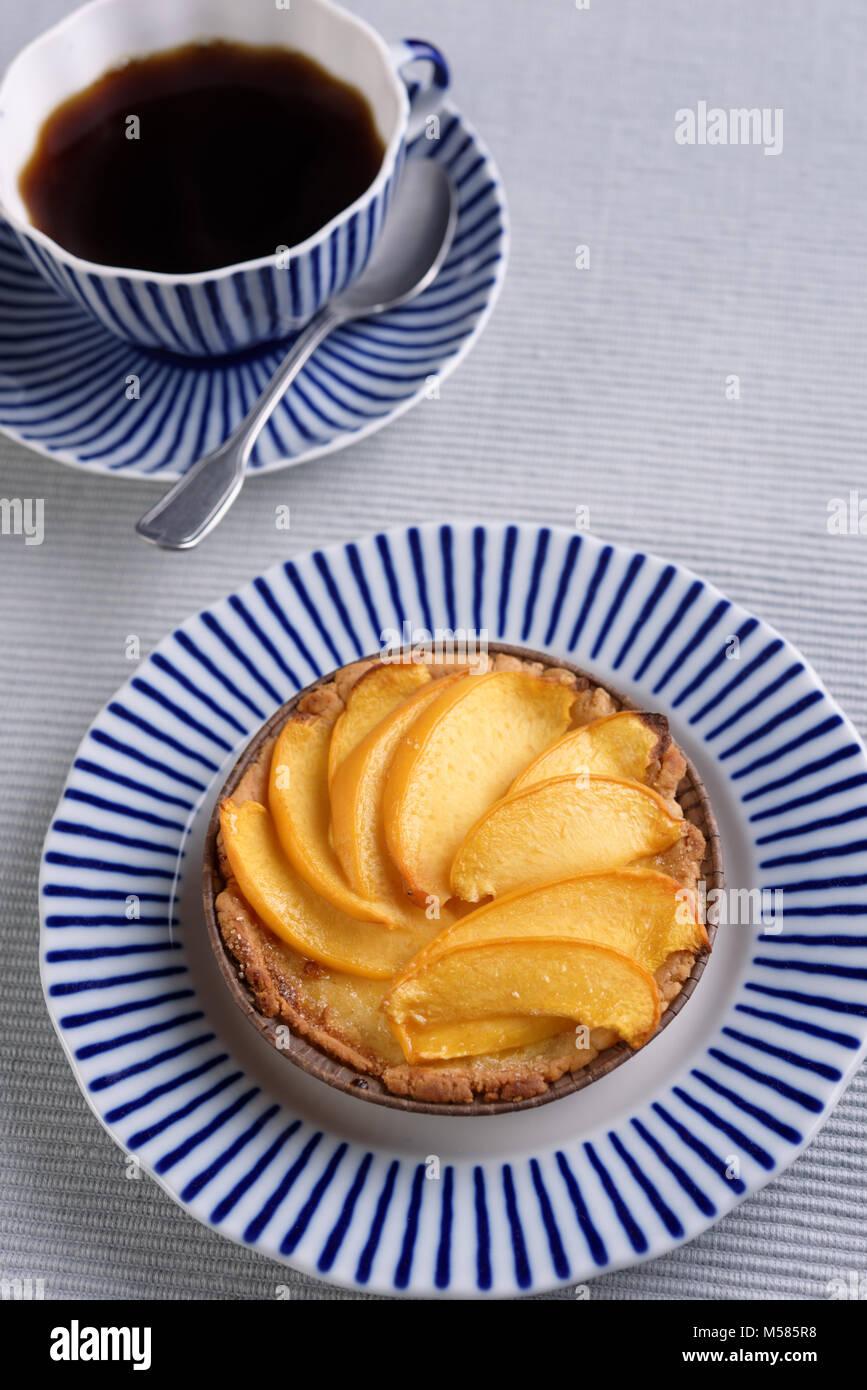 Peach tart and black coffee - Stock Image