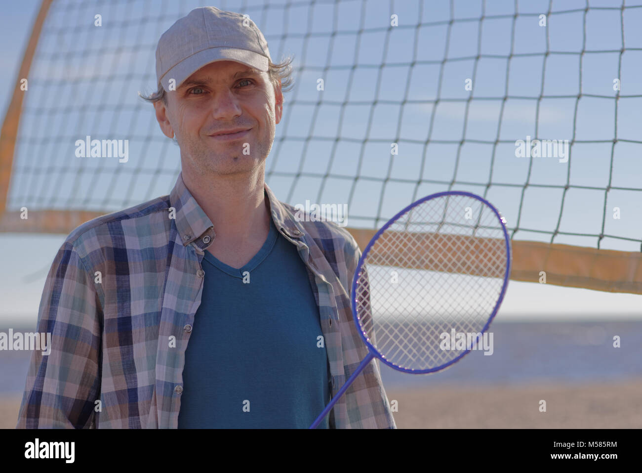 Mature man with badminton racket on a beach - Stock Image