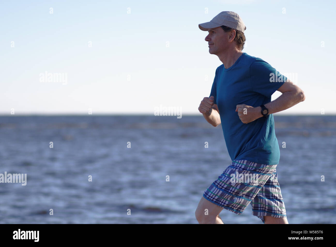Mature man during jogging on a beach - Stock Image